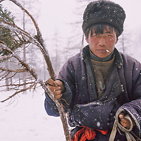 Duujii, returning from helping other nomads cross Utreg Pass, carries a juniper branch as part of a spiritual ritual in Darhad Valley, Mongolia.
