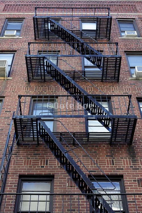 fire escapes dominate the facades of typical brownstone apartment buildings New York City