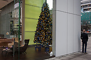 A distorted businessman and a bystander at the Aviva office foyer in front of a Christmas tree at the insurance corporate's HQ, on 9th December 2016, in the City of London.