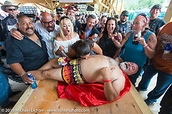 Big Sexy does body shots with the wedding party he was partaking in at the Easyriders Saloon during the annual Sturgis Black Hills Motorcycle Rally. Sturgis, SD, USA. August 5, 2014.  Photography ©2014 Michael Lichter.