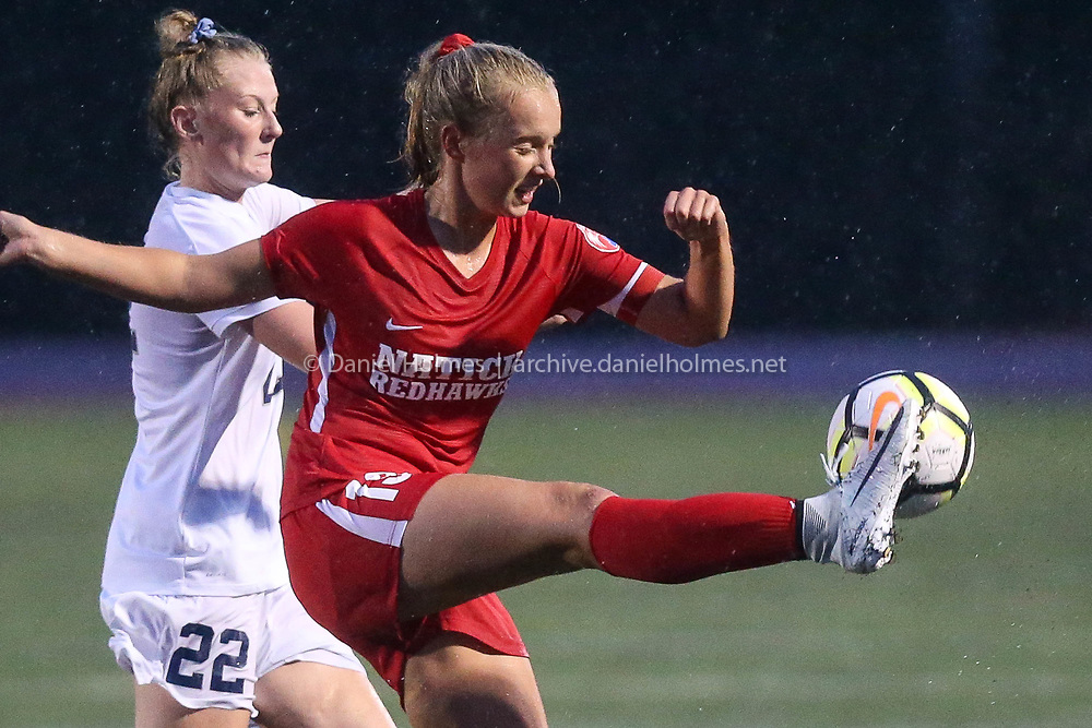 (9/25/18, NATICK, MA) Natick's Hailey Murphy connects with the ball with Framingham's Shannon Walker pressuring during the girls soccer game at Natick High School on Tuesday. [Daily News and Wicked Local Photo/Dan Holmes]