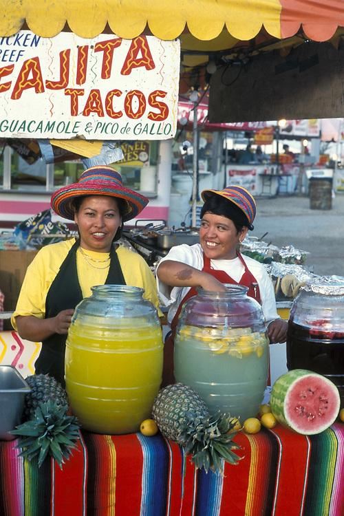 Two Hispanic woman making lemonade and preparing food at Fajita/Taco stand at Texas Rodeo in Travis County.<br /> ©Bob Daemmrich/