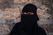 Amina stands for a portrait in a narrow street in Lamu, Kenya.