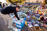 """15 JANUARY 2010 - TUCSON, AZ:  A man leaves a note for Congresswoman Gabrielle Giffords at a memorial at her office in Tucson, AZ, Saturday, January 15. Six people were killed and 14 injured in the shooting spree at a """"Congress on Your Corner"""" event hosted by Arizona Congresswoman Gabrielle Giffords at a Safeway grocery store in north Tucson on January 8. Congresswoman Giffords, the intended target of the attack, was shot in the head and seriously injured in the attack but is recovering. Doctors announced that they removed her breathing tube Saturday, one week after the attack. The alleged gunman, Jared Lee Loughner, was wrestled to the ground by bystanders when he stopped shooting to reload the Glock 19 semi-automatic pistol. Loughner is currently in federal custody at a medium security prison near Phoenix.      PHOTO BY JACK KURTZ"""