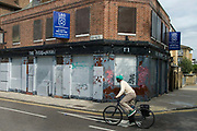 East London June 2009.Derelict pub called The Overdraught with cyclist passing.