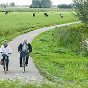Nederland Delft 17-09-2010 20100917     A4 Delft - Schiedam wordt definitief verlengd,  er  is begin deze maand officieel besloten tot de aanleg van het stuk snelweg waarover zo'n vijftig jaar is gesproken. Natuurgebied dat in de toekomst zal moeten wijken na het doortrekken van de A4. Senioren met kleinkind fietsen op fietspad fietsroute door natuurgebied. oppassen Rijkswaterstaat en het ministerie van VWS hebben dat laten weten.Over de nieuwe verkeersader wordt al decennialang gesteggeld, vooral omdat de weg het natuurgebied Midden-Delfland doorboort...De zeven kilometer asfalt tussen Delft en Schiedam doorkruist straks verdiept of via een tunnel het natuurgebied tussen de twee steden. Het belangrijkste pluspunt is dat de A13 wordt ontlast. Op rijksweg A13 staat dagelijks de voor de economie schadelijkste file van Nederland. Met het project A4 Delft-Schiedam willen lokale en regionale overheden en het Rijk de problemen rond bereikbaarheid en leefbaarheid op en rond de A13 en de A4 Delft-Schiedam oplossen. Midden Delftland. , Ruimtelijke plannen, ruimtelijke planning, ruimtelijke visie, ruraal, rurale omgeving, rustiek, rustieke, rustieke omgeving, rustig, rustige, senior, senioren, space, spare time, sportief, sportieve, sportive, stedelijke vernieuwing, stil, streekplan, sunny, terrein, The Netherlands Holland Nederland, toekomst, toekomstige plannen, toekomstplannen, tracé, traject, uitgestrektheid, verbinding, verbindingen, vergezicht, vergezichten, verkeer en vervoer, verkeer en waterstaat, verkeersnet, verlengen, vernieuwing, vervoer, vewezenlijken, vitaal, vitale, vitaliteit, vrije tijd, vrouw, vrouwen, wegenbouw, wegenbouwplanologie, wegennet, wegnet, wegverbinding, wei, weide, weidegang, weiland, wijds, wijdsheid