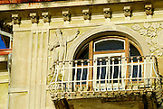 Detail of building facade with balcony, arched window, and intricate figures in bas relief. Opatija, Croatia