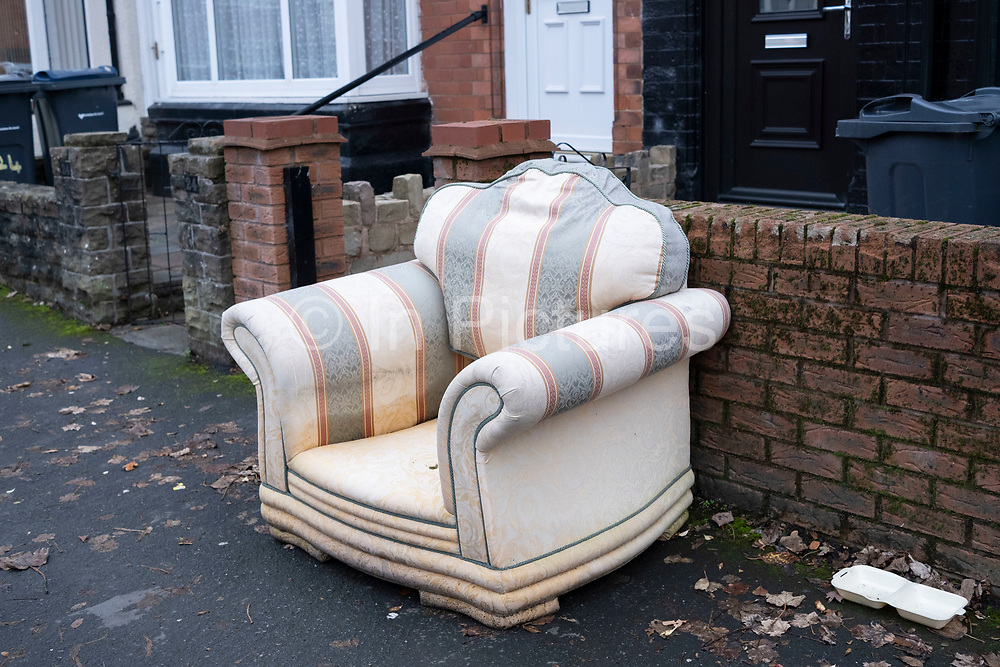 Old armchair dumped at a main road junction in Bordesley on 21st November 2020 in Birmingham, United Kingdom. Illegal dumping, also called fly dumping or fly tipping, is the dumping of waste illegally instead of using an authorised method such as kerbside collection or using an authorised rubbish dump. It is the illegal deposit of any waste onto land, including waste dumped or tipped on a site with no licence to accept waste.