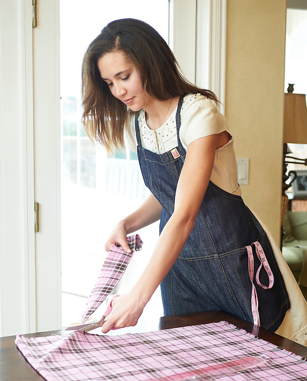 brunette lady wearing an apron cutting fabric for sewing