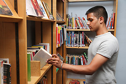 Student in library looking at books.