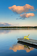 Clouds reflected in Silent Lake with Muskoka chair on dock<br />Silent Lake Provincial Park<br />Ontario<br />Canada