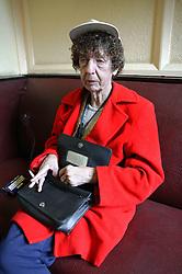 Woman smoking a cigarette in a pub,