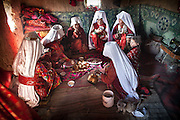 Visiting guests for a wedding are sitting to eat fried dough, candies and drink salty milk tea..The veil celebration: before moving to her new husband's camp, Ikhbal, a recently married Kyrgyz girl, will exchange the red veil of the unmarried girl for the white veil signifying that she is now a married woman..The Kyrgyz settlement of Ech Keli, above Chaqmaqtin lake, Er Ali Boi's camp...Trekking through the high altitude plateau of the Little Pamir mountains, where the Afghan Kyrgyz community live all year, on the borders of China, Tajikistan and Pakistan.