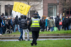© Licensed to London News Pictures. 06/12/2020. Manchester, UK. A Police Officer watches over a crowd in Piccadilly Gardens during a Rise Up protest in Manchester. Photo credit: Kerry Elsworth/LNP