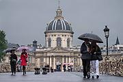 France, Paris, Couple walking in rain on the Pont des Arts, i'Intitut de France behind
