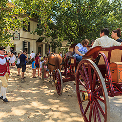 A costumed colonist photographs tourists on a horse carriage at Colonial Williamsburg, VA.