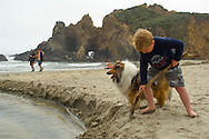 Young boy playing with stick in sand along creek at Pfeiffer Beach, Big Sur Coast, Monterey County, California