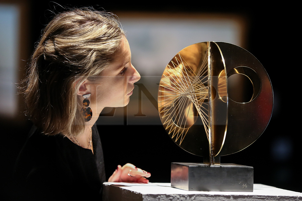 """© Licensed to London News Pictures. 12/11/2018. London, UK. A staff member looks at """"Mincarlo"""" By Dame Barbara Hepworth (1903- 1975) - polished bronze and string on a slate base (Estimate £80,000-120,000).<br /> <br /> Bonhams Modern British and Irish Art photocall. Auction to be held on 14 November 2018. Photo credit: Dinendra Haria/LNP"""