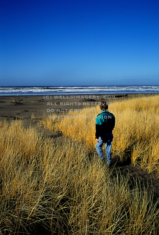 Image of a woman walking along a beach path to Klipsan Beach in Long Beach, Washington, Pacific Northwest, model released by Randy Wells