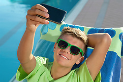 Boy swimming pool sunglasses taking selfie picture