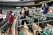 17 SEPTEMBER 2020 - DES MOINES, IOWA: People watch a naturalization ceremony at Principal Park, a minor league baseball stadium in downtown Des Moines. About 75 people from 32 countries were naturalized as US citizens Thursday. It was the last citizenship ceremony in Des Moines before citizenship fees dramatically increase. Starting Oct. 2, the fee to apply for U.S. citizenship will increase from $640 to $1,160 if filed online, or $ 1,170 in paper filing, a more than 80% increase in cost. Advocates for immigration are afraid the new fees will be too expensive for many immigrants and say it's an effort by the Trump Administration to limit the number of new citizens welcomed into the United States. Because of the COVID-19 pandemic, there has been dramatic slow down in the number of naturalization ceremonies this year.           PHOTO BY JACK KURTZ