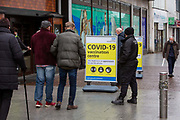 Elderly residents of Folkestone and the surrounding area line up to receive their first vaccine against COVID-19 outside the converted Debenhams store mass vaccination centre in the town centre on the 27th of January 2021 in Folkestone, Kent, United Kingdom.  The centre is being run by Kent Community Health NHS Foundation Trust KCHFT, which has enlisted an army of vaccinators and support staff to deliver the jabs.