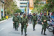 """01 FEBRUARY 2014 - BANGKOK, THAILAND: Thai soldiers walk into a polling place to secure it early Sunday morning. Security at many polling places was provided by the Thai army. Thais went to the polls in a """"snap election"""" Sunday called in December after Prime Minister Yingluck Shinawatra dissolved the parliament in the face of large anti-government protests in Bangkok. The anti-government opposition, led by the People's Democratic Reform Committee (PDRC), called for a boycott of the election and threatened to disrupt voting. Many polling places in Bangkok were closed by protestors who blocked access to the polls or distribution of ballots. The result of the election are likely to be contested in the Thai Constitutional Court and may be invalidated because there won't be quorum in the Thai parliament.    PHOTO BY JACK KURTZ"""