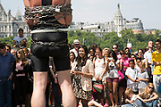 Street performing escapologist Tony Roberts delights crowds of tourists with his show on the Southbank in London, UK. His performance in incredibly entertaining, encapsulating the crowd of people gathered as he escapes from tightly being bound in chains. As a consequence, he makes a lot of money which people drop into his hat after the show. The South Bank is a significant arts and entertainment district, and home to an endless list of activities for Londoners, visitors and tourists alike.