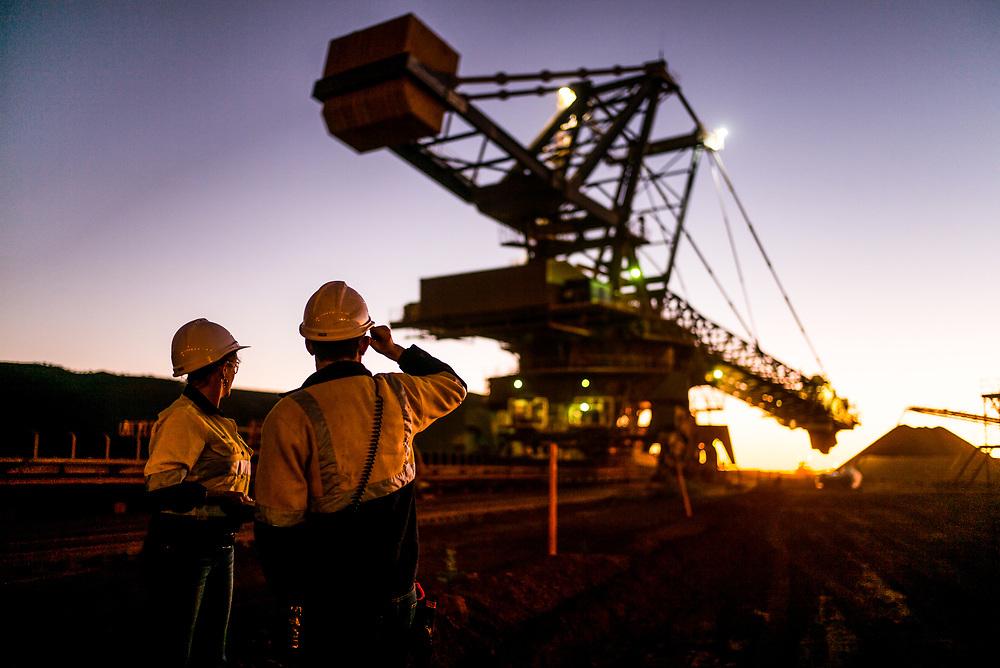 Workers watch an iron ore reclaimer work at dawn in the Pilbarra region in Western Australia.