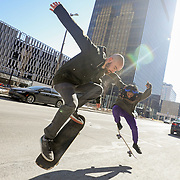 """Ryan Gongaware (cq), of Bowling Green, left, and Osi Okoro (cq), of Toledo, practice their skateboarding tricks at Madison Avenue and St. Clair Street in downtown Toledo on Friday, Feb. 26, 2021. """"The snow has finally melted,"""" Mr. Gongaware said. He says he frequently comes up to Toledo. THE BLADE/KURT STEISS"""