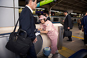 woman cleaning escalator railing while some businessmen walk by Japan Tokyo
