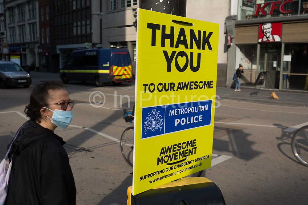 With the Coronavirus lockdown continuing into the Bank Holiday weekend, when Prime Minister Boris Johnson is due to tell the nation that only a gradual easing of regulations and social distancing rules are still to be in place, a person wearing a surgical mask prepares to cross Bishopsgate where a sign that supports emergency services workers such as the police has been attached to a crossing post in the City of London, the capitals financial district, on 7th May 2020, in London, England.