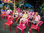 "18 AUGUST 2014 - BANGKOK, THAILAND: The audience watches the Lehigh Leng Kaitoung Opera troupe perform during a performance at Chaomae Thapthim Shrine, a small Chinese shrine in a working class neighborhood of Bangkok. The performance was for Ghost Month. Chinese opera was once very popular in Thailand, where it is called ""Ngiew."" It is usually performed in the Teochew language. Millions of Chinese emigrated to Thailand (then Siam) in the 18th and 19th centuries and brought their culture with them. Recently the popularity of ngiew has faded as people turn to performances of opera on DVD or movies. There are still as many 30 Chinese opera troupes left in Bangkok and its environs. They are especially busy during Chinese New Year and Chinese holiday when they travel from Chinese temple to Chinese temple performing on stages they put up in streets near the temple, sometimes sleeping on hammocks they sling under their stage. Most of the Chinese operas from Bangkok travel to Malaysia for Ghost Month, leaving just a few to perform in Bangkok.        PHOTO BY JACK KURTZ"