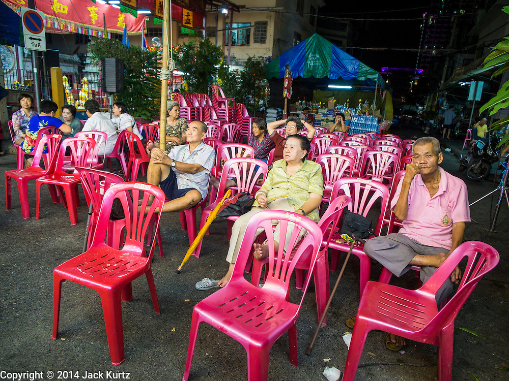 """18 AUGUST 2014 - BANGKOK, THAILAND: The audience watches the Lehigh Leng Kaitoung Opera troupe perform during a performance at Chaomae Thapthim Shrine, a small Chinese shrine in a working class neighborhood of Bangkok. The performance was for Ghost Month. Chinese opera was once very popular in Thailand, where it is called """"Ngiew."""" It is usually performed in the Teochew language. Millions of Chinese emigrated to Thailand (then Siam) in the 18th and 19th centuries and brought their culture with them. Recently the popularity of ngiew has faded as people turn to performances of opera on DVD or movies. There are still as many 30 Chinese opera troupes left in Bangkok and its environs. They are especially busy during Chinese New Year and Chinese holiday when they travel from Chinese temple to Chinese temple performing on stages they put up in streets near the temple, sometimes sleeping on hammocks they sling under their stage. Most of the Chinese operas from Bangkok travel to Malaysia for Ghost Month, leaving just a few to perform in Bangkok.        PHOTO BY JACK KURTZ"""