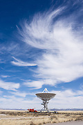 """Swirling cirrus clouds over Very Large Array (VLA) radio astronomy telescope, near Socorro, New Mexico, USA. The Karl G. Jansky Very Large Array (VLA) is one of the world's premier astronomical radio observatories. Visit the VLA on the Plains of San Agustin fifty miles west of Socorro, between the towns of Magdalena and Datil, in New Mexico, USA. US Route 60 passes through the scientific complex, which welcomes visitors. The VLA is a set of 27 movable radio antennas on tracks in a Y-shape. Each antenna is 25 meters (82 feet) in diameter. The data from the antennas is combined electronically to give the resolution of an antenna 36km (22 miles) across, with the sensitivity of a dish 130 meters (422 feet) in diameter. After being built 1973-1980, the VLA's electronics and software were significantly upgraded from 2001-2012 by at least an order of magnitude in both sensitivity and radio-frequency coverage. The VLA is a component of the National Radio Astronomy Observatory (NRAO). Astronomers using the VLA have made key observations of black holes and protoplanetary disks around young stars, discovered magnetic filaments and traced complex gas motions at the Milky Way's center, probed the Universe's cosmological parameters, and provided new knowledge about interstellar radio emission. The VLA was prominently featured in the 1997 film """"Contact,"""" a classic science fiction drama film adapted from the Carl Sagan novel, with Jodie Foster portraying the film's protagonist, Dr. Eleanor """"Ellie"""" Arroway, a SETI scientist who finds strong evidence of extraterrestrial life."""