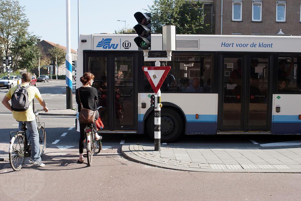 Een stadsbus blokkeert fietsers de doorgang, terwijl zij groen licht hebben..<br /> <br /> A city bus is blocking the way for cyclist at a traffic light.
