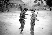 A Karen National Liberation Army guerrilla shares a fun moment with a recently recruited child guerrilla. Both the government of Burma and guerrilla factions opposing the military junta use children as combatants.