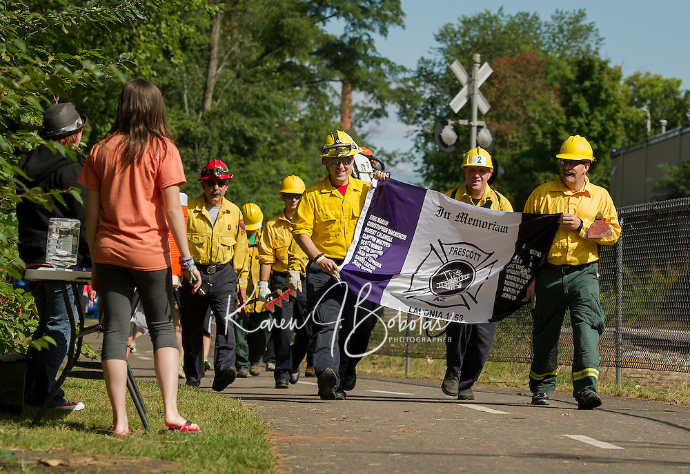 Members of Laconia Fire Department march in memoriam to the fallen Arizona Firefighters during Saturday's WOW Trail Walk during the WOW Fest festivities in Laconia.  (Karen Bobotas/for the Laconia Daily Sun)
