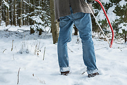 Young man with a saw in forest in winter, Bavaria, Germany