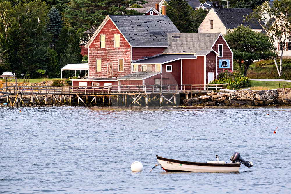 The red Salt Box style building housing the H2Outfitters and Salt Cod Cafe across Wills Gut on Orrs Island, Maine.
