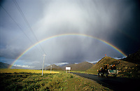 A full rainbow forms over the Tibetan countryside as Tibetans travel west in the back of a truck.