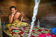 29 OCTOBER 2012 - MAYO, PATTANI, THAILAND: A resident eats in his room at the Bukit Kong home in Mayo, Pattani. He said he is a survivor of the Tak Bai incident in which the Thai army killed more than 80 people protesting against the government. He said he didn't remember his name or how he came to be at the home. The home opened 27 years ago as a Pondo School, or traditional Islamic school, in the Mayo district of Pattani. Shortly after it opened, people asked the headmaster to look after individuals with mental illness. The headmaster took them in and soon the school was a home for the mentally ill. Thailand has limited mental health facilities and most are in Bangkok, more than 1,100 kilometers (650 miles) away. The founder died suddenly in 2006 and now his widow, Nuriah Jeteh, struggles to keep the home open. Facilities are crude by western standards but the people who live here have nowhere else to go. Some were brought here by family, others dropped off by the military or police. The home relies on donations and gets no official government support, although soldiers occasionally drop off food. Now there are only six patients, three of whom are kept chained in their rooms.  Jeteh says she relies on traditional Muslim prayers, holy water and herbal medicines to treat the residents. Western style drugs are not available and they don't have a medic on staff.     PHOTO BY JACK KURTZ