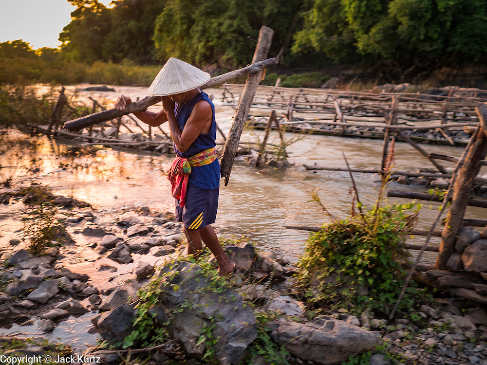 19 JUNE 2016 - DON KHONE, CHAMPASAK, LAOS: A fisherman carries a part of one of his fish traps back to shore at Khon Pa Soi Waterfalls, on the east side of Don Khon. It's the smaller of the two waterfalls in Don Khon. Fishermen have constructed an elaborate system of rope bridges over the falls they use to get to the fish traps they set. Fishermen in the area are contending with lower yields and smaller fish, threatening their way of life. The Mekong River is one of the most biodiverse and productive rivers on Earth. It is a global hotspot for freshwater fishes: over 1,000 species have been recorded there, second only to the Amazon. The Mekong River is also the most productive inland fishery in the world. The total harvest of fish from the Mekong is approximately 2.5 million metric tons per year. By some estimates the harvest in the Tonle Sap (in Cambodia) had doubled from 1940 to 1995, but the number of people fishing the in the lake has quadrupled, so the harvest per person is cut in half. There is evidence of over fishing in the Mekong - populations of large fish have shrunk and fishermen are bringing in smaller and smaller fish.     PHOTO BY JACK KURTZ
