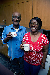 Older couple drinking tea in the kitchen smiling,