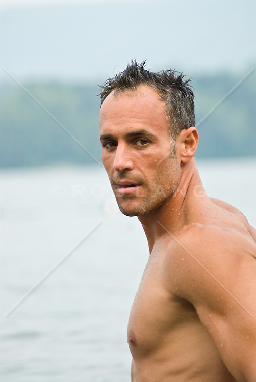 Wet shirtless man looking back toward camera