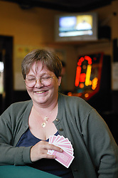 Woman playing a game of cards in a pub,