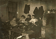 Group of women in a New York sweatshop making garments. In the foreground are sewing machines. Young girl by the fireplace is probably 14-years old. Photograph February 1908.