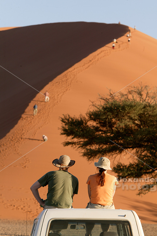 Ready to watch the sunset play across Dune 45 as travelers struggle climb it, Namibia