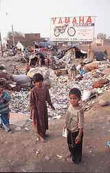 Young children in Shanty town on outskirts of Patiala; Punjab; India; with plastic tents and Yamaha motorbike advert in the background,