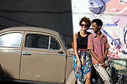 Actors Bruno Barbosa and Luzia Avellar Liron in front of an old beetle car in the street in Vidigal. Since pacification in 2011, Vidigal has slowly become known as what some call a model favela, seen as the safest favela in Rio, home to a mixed community which now includes foreigners, hostels, restaurants, theatres and creative businesses.